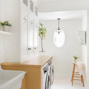 Esempio di una lavanderia multiuso country di medie dimensioni con lavello da incasso, ante a filo, ante gialle, lavatrice e asciugatrice affiancate, pavimento bianco e top giallo