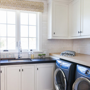 Inspiration for a nautical l-shaped separated utility room in Orange County with a submerged sink, white cabinets, white walls, a side by side washer and dryer, beige floors, black worktops and shaker cabinets.