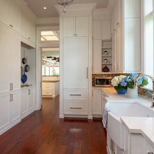 Example of a mid-sized island style galley medium tone wood floor and brown floor utility room design in Miami with a farmhouse sink, raised-panel cabinets, white cabinets, quartzite countertops, white walls, a side-by-side washer/dryer and white countertops