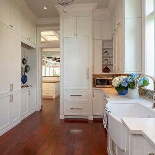 Idéer för mellanstora tropiska parallella vitt grovkök, med en rustik diskho, luckor med upphöjd panel, vita skåp, bänkskiva i kvartsit, vita väggar, mellanmörkt trägolv, en tvättmaskin och torktumlare bredvid varandra och brunt golv