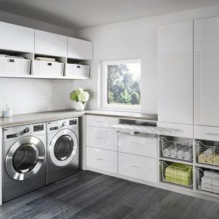 Bild på en funkis l-formad tvättstuga, med släta luckor, vita skåp, bänkskiva i kvartsit, vita väggar, klinkergolv i porslin och en tvättmaskin och torktumlare bredvid varandra