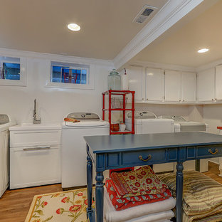 Design ideas for a large classic l-shaped utility room in Santa Barbara with an utility sink, recessed-panel cabinets, white cabinets, wood worktops, beige walls, medium hardwood flooring, a side by side washer and dryer, brown floors and red worktops.