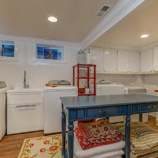 Foto på ett stort vintage röd l-format grovkök, med en allbänk, luckor med infälld panel, vita skåp, träbänkskiva, beige väggar, mellanmörkt trägolv, en tvättmaskin och torktumlare bredvid varandra och brunt golv