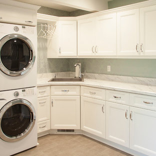 Design ideas for a contemporary laundry room in Chicago with an undermount sink, recessed-panel cabinets, white cabinets, marble benchtops, green walls, plywood floors and a stacked washer and dryer.