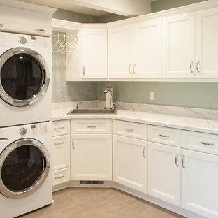 Idee per una lavanderia minimal con lavello sottopiano, ante con riquadro incassato, ante bianche, top in marmo, pareti verdi, pavimento in compensato e lavatrice e asciugatrice a colonna