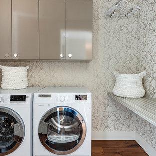 Inspiration pour une buanderie minimaliste dédiée avec des portes de placard beiges, un mur multicolore, un sol en bois brun et des machines côte à côte.