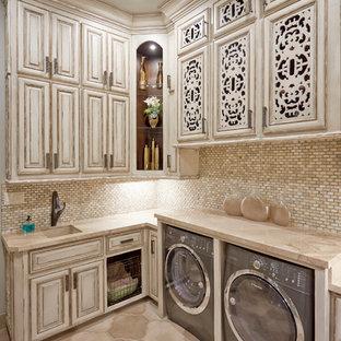 Idee per una sala lavanderia mediterranea con lavello sottopiano, ante con bugna sagomata, ante in legno chiaro, top in quarzite, pareti beige, pavimento in cemento, lavatrice e asciugatrice affiancate e pavimento beige