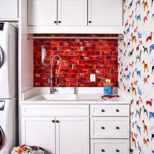 Ispirazione per una lavanderia tradizionale con lavello a vasca singola, ante in stile shaker, ante bianche, pareti multicolore, lavatrice e asciugatrice a colonna, pavimento rosso e top bianco