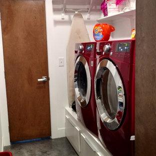 Imagen de cuarto de lavado de galera, ecléctico, pequeño, con armarios con paneles lisos, puertas de armario blancas, paredes blancas, suelo de cemento y lavadora y secadora juntas