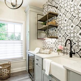 Idée de décoration pour une buanderie parallèle champêtre multi-usage et de taille moyenne avec un évier de ferme, un placard à porte shaker, des portes de placard grises, un plan de travail en quartz, un mur beige, un sol en vinyl, des machines côte à côte, un sol multicolore et un plan de travail blanc.