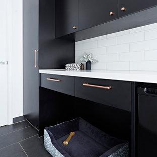 Immagine di una sala lavanderia moderna di medie dimensioni con lavello sottopiano, ante nere, lavatrice e asciugatrice a colonna, pavimento nero, top bianco, top in quarzo composito e pareti bianche