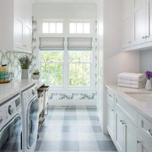 Foto på en mellanstor vintage vita parallell tvättstuga enbart för tvätt, med en undermonterad diskho, luckor med infälld panel, vita skåp, bänkskiva i kvarts, grå väggar, linoleumgolv, en tvättmaskin och torktumlare bredvid varandra och grått golv