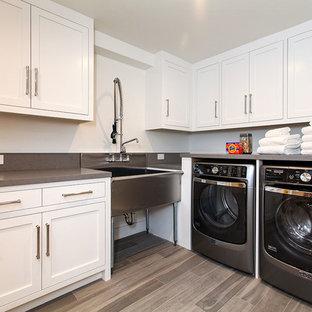Foto på en mycket stor vintage grå l-formad tvättstuga enbart för tvätt, med luckor med infälld panel, vita skåp, bänkskiva i kvarts, vita väggar, klinkergolv i porslin, en tvättmaskin och torktumlare bredvid varandra, en allbänk och beiget golv