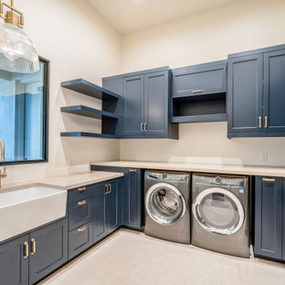 Example of a large trendy u-shaped porcelain tile, white floor and vaulted ceiling dedicated laundry room design in Phoenix with a farmhouse sink, shaker cabinets, blue cabinets, quartzite countertops, beige walls, a side-by-side washer/dryer and beige countertops