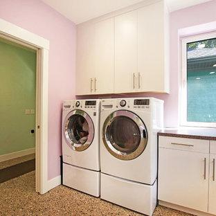 Exempel på ett mycket stort 50 tals flerfärgad u-format flerfärgat grovkök, med en nedsänkt diskho, släta luckor, grå skåp, laminatbänkskiva, rosa väggar, betonggolv, en tvättmaskin och torktumlare bredvid varandra och flerfärgat golv