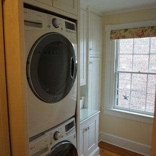 Klassisk inredning av en liten parallell tvättstuga enbart för tvätt, med vita skåp, bänkskiva i glas, beige väggar, mörkt trägolv, en tvättpelare och luckor med upphöjd panel