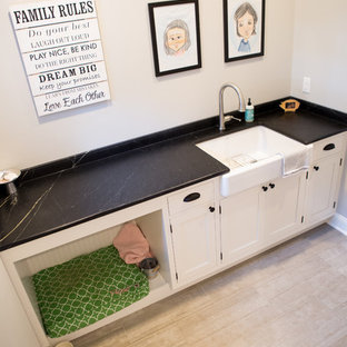 Medium sized classic single-wall utility room in New York with a belfast sink, beaded cabinets, white cabinets, soapstone worktops, grey walls, porcelain flooring and black worktops.