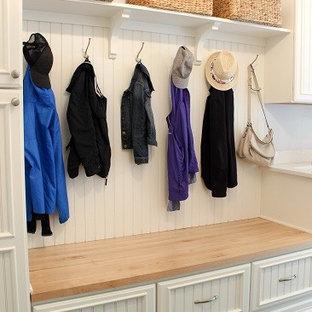 Bild på ett mellanstort vintage linjärt grovkök, med en rustik diskho, luckor med infälld panel, vita skåp, träbänkskiva, lila väggar, klinkergolv i porslin, en tvättmaskin och torktumlare bredvid varandra och grått golv