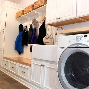 Exempel på ett mellanstort klassiskt linjärt grovkök, med en rustik diskho, luckor med infälld panel, vita skåp, träbänkskiva, lila väggar, klinkergolv i porslin, en tvättmaskin och torktumlare bredvid varandra och grått golv
