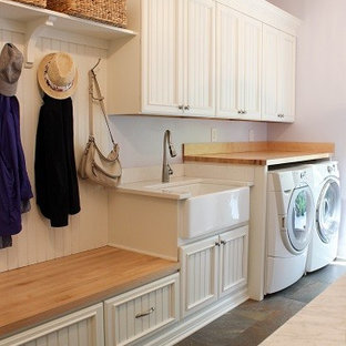 Photo of a mid-sized traditional single-wall utility room in Other with a farmhouse sink, recessed-panel cabinets, white cabinets, wood benchtops, purple walls, porcelain floors, a side-by-side washer and dryer and grey floor.