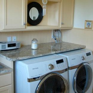 Idéer för mellanstora maritima grovkök, med en nedsänkt diskho, luckor med infälld panel, gula skåp, granitbänkskiva, vita väggar, en tvättmaskin och torktumlare bredvid varandra och gult golv