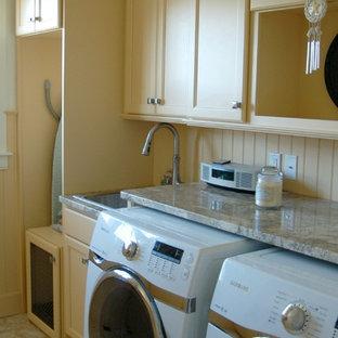 Foto på ett mellanstort maritimt grovkök, med en nedsänkt diskho, luckor med infälld panel, gula skåp, granitbänkskiva, vita väggar, en tvättmaskin och torktumlare bredvid varandra och gult golv