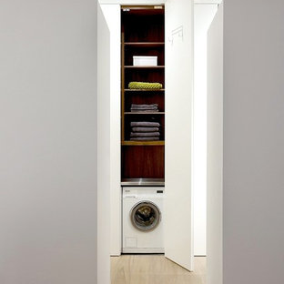 Inspiration for a small modern light wood floor laundry closet remodel in New York with white walls, flat-panel cabinets, white cabinets and a concealed washer/dryer