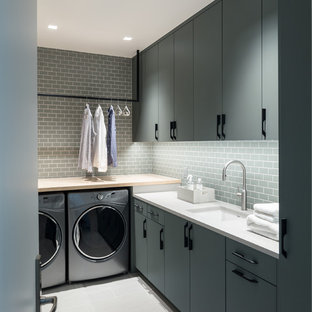 Dedicated laundry room - mid-sized contemporary l-shaped gray floor dedicated laundry room idea in Other with flat-panel cabinets, a side-by-side washer/dryer, an undermount sink, gray cabinets, wood countertops and white countertops