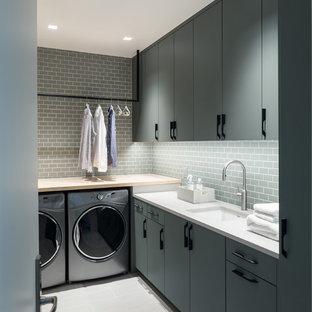 他の地域の中くらいのコンテンポラリースタイルのおしゃれな洗濯室 (フラットパネル扉のキャビネット、左右配置の洗濯機・乾燥機、アンダーカウンターシンク、グレーのキャビネット、木材カウンター、グレーの床、白いキッチンカウンター、L型) の写真