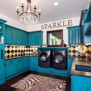 Immagine di una grande sala lavanderia chic con lavello sottopiano, ante con bugna sagomata, ante blu, pareti bianche, lavatrice e asciugatrice affiancate, pavimento marrone e top nero