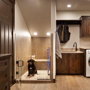 Cette image montre une buanderie chalet multi-usage avec un évier encastré, des portes de placard en bois sombre et un mur blanc.