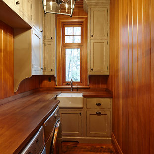 Example of a mid-sized mountain style l-shaped medium tone wood floor dedicated laundry room design in Toronto with a farmhouse sink, recessed-panel cabinets, distressed cabinets, wood countertops and a side-by-side washer/dryer