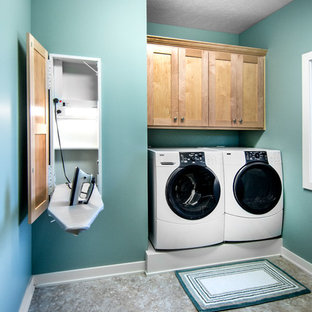 Example of a small arts and crafts single-wall linoleum floor dedicated laundry room design in Omaha with shaker cabinets, blue walls, a side-by-side washer/dryer and medium tone wood cabinets