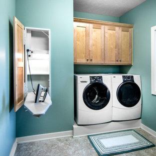 Foto på en liten amerikansk linjär tvättstuga enbart för tvätt, med skåp i shakerstil, blå väggar, linoleumgolv, en tvättmaskin och torktumlare bredvid varandra och skåp i mellenmörkt trä