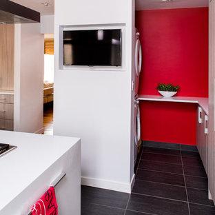 Esempio di una piccola sala lavanderia minimal con ante lisce, ante in legno chiaro, top in quarzo composito, pareti rosse, pavimento in gres porcellanato, lavatrice e asciugatrice a colonna e pavimento grigio