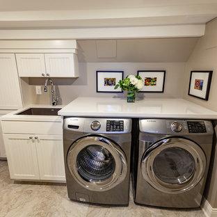 Exempel på en stor klassisk vita linjär vitt tvättstuga enbart för tvätt, med en undermonterad diskho, luckor med profilerade fronter, vita skåp, marmorbänkskiva, beige väggar, vinylgolv, en tvättmaskin och torktumlare bredvid varandra och beiget golv