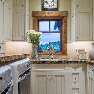 Bild på en mellanstor lantlig u-formad tvättstuga enbart för tvätt, med en undermonterad diskho, luckor med infälld panel, beige skåp, beige väggar och en tvättmaskin och torktumlare bredvid varandra