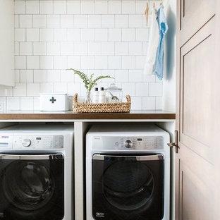 Eklektisk inredning av en mellanstor bruna brunt tvättstuga, med träbänkskiva, vita väggar, tegelgolv, en tvättmaskin och torktumlare bredvid varandra och svart golv