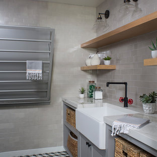 This is an example of a large classic utility room in Los Angeles with a belfast sink, shaker cabinets, grey cabinets, engineered stone countertops, concrete flooring and multi-coloured floors.