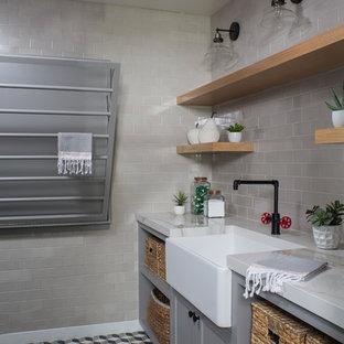 Bild på en stor vintage tvättstuga, med en rustik diskho, skåp i shakerstil, grå skåp, bänkskiva i kvarts, betonggolv och flerfärgat golv