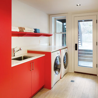 Example of a mid-sized trendy single-wall light wood floor utility room design in New York with an undermount sink, flat-panel cabinets, red cabinets, quartz countertops, white walls, a side-by-side washer/dryer and white countertops