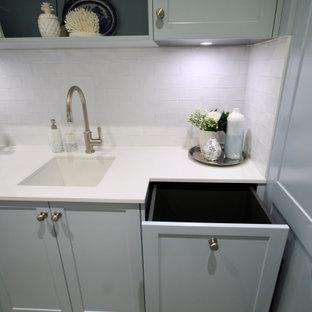 Idéer för en mellanstor klassisk vita u-formad tvättstuga enbart för tvätt, med en undermonterad diskho, skåp i shakerstil, blå skåp, bänkskiva i kvarts, vitt stänkskydd, stänkskydd i tunnelbanekakel, vita väggar, ljust trägolv, en tvättpelare och brunt golv