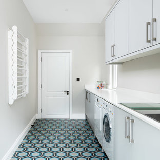 This is an example of a contemporary single-wall separated utility room in London with flat-panel cabinets, grey cabinets, grey walls, a side by side washer and dryer, multi-coloured floors and white worktops.