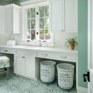 Foto di una sala lavanderia con ante bianche, top in quarzo composito, pareti verdi, lavatrice e asciugatrice affiancate, top bianco e ante con riquadro incassato