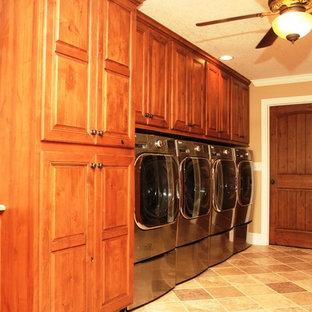 Idéer för att renovera en stor vintage linjär tvättstuga enbart för tvätt, med luckor med upphöjd panel, skåp i mellenmörkt trä, granitbänkskiva, beige väggar, klinkergolv i keramik, en tvättmaskin och torktumlare bredvid varandra och beiget golv