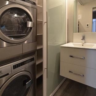 Bild på en liten funkis linjär liten tvättstuga, med luckor med glaspanel, vita skåp, grå väggar, klinkergolv i porslin, en tvättpelare och brunt golv