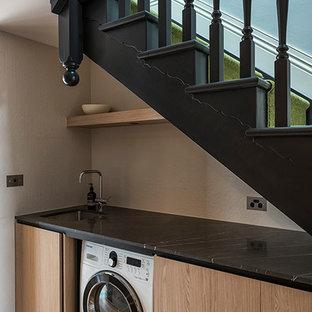 Immagine di una piccola lavanderia multiuso minimalista con ante in legno scuro, pavimento in legno massello medio, lavatrice e asciugatrice nascoste, ante lisce, top in marmo, pareti beige, top nero e lavello sottopiano