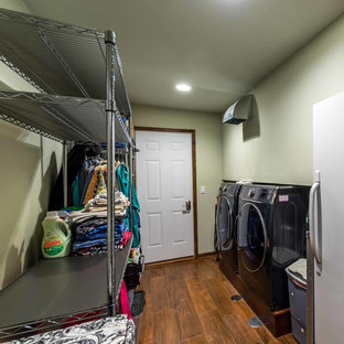 Mid-sized country galley utility room in Chicago with open cabinets, stainless steel cabinets, yellow walls, ceramic floors and a side-by-side washer and dryer.