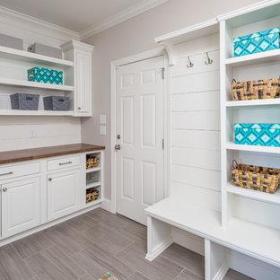 Foto di una grande sala lavanderia classica con ante bianche, top in legno, pareti grigie, lavatrice e asciugatrice affiancate, pavimento in laminato, pavimento marrone, top marrone e ante a filo