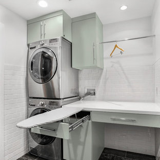 Inredning av en retro mellanstor linjär tvättstuga enbart för tvätt, med släta luckor, bänkskiva i koppar, vita väggar, klinkergolv i porslin, en tvättpelare, grått golv och gröna skåp
